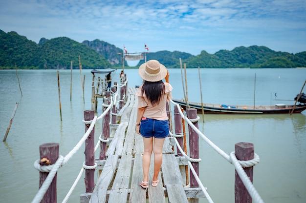 Femme debout sur une jetée en bois à la baie de talet, khanom, nakhon si thammarat, thaïlande