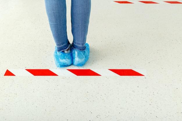 Femme debout en ligne en gardant la distance sociale portant des couvre-chaussures, couvre-chaussures médicales à l'hôpital. personnes se tenant derrière une ligne d'avertissement pendant le coronavirus covid 19. distanciation sociale. jambes en ligne
