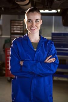 Femme debout mécanicien à un garage de réparation