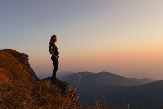 Femme debout sur une montagne en regardant au coucher du soleil