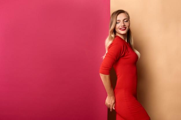 Femme debout sur le mur de la marque claire avec copyspace