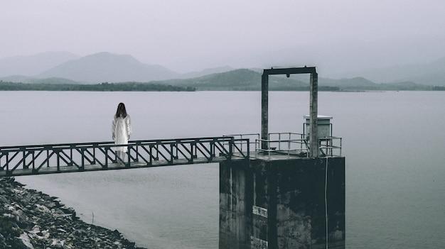 Femme debout à la porte de niveau d'eau, scène d'horreur dans le ton blanc