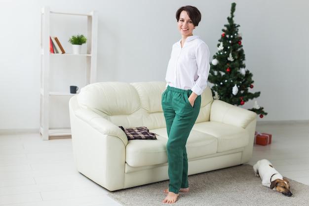 Femme debout près d'un arbre de noël dans le salon