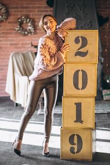 Femme debout près des boîtes 2019 à noël