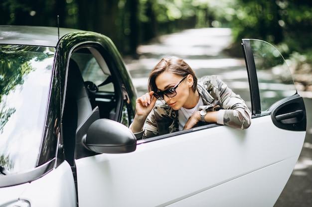 Femme debout près de la voiture dans le parc