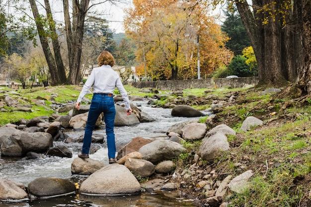 Femme, debout, sur, rivière, rochers