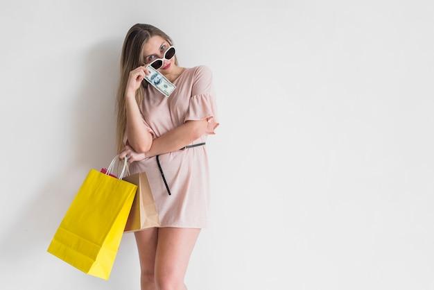 Femme debout avec des sacs à provisions et de l'argent