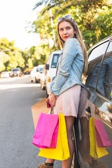 Femme debout avec des sacs à provisions en voiture