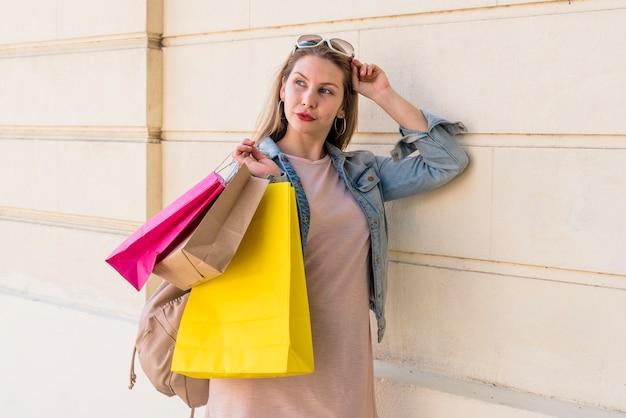 Femme debout avec des sacs de shopping lumineux au mur
