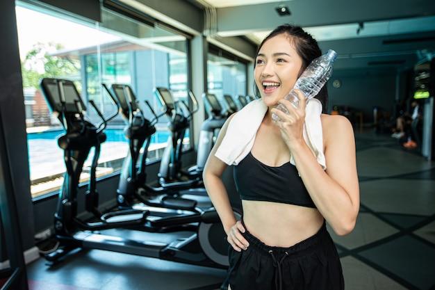 Femme debout et se détendre après l'exercice, tenant une bouteille d'eau pour toucher le visage.