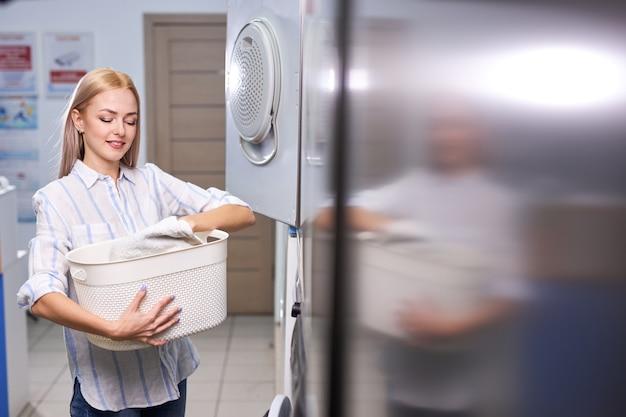 Femme debout seule avec des vêtements propres dans la buanderie avec sèche-linge. femme en tenue décontractée tient le bassin avec des vêtements, heureuse après avoir obtenu des serviettes propres