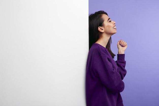 Femme debout et souriant aux côtés de mur de panneau d'affichage blanc vide