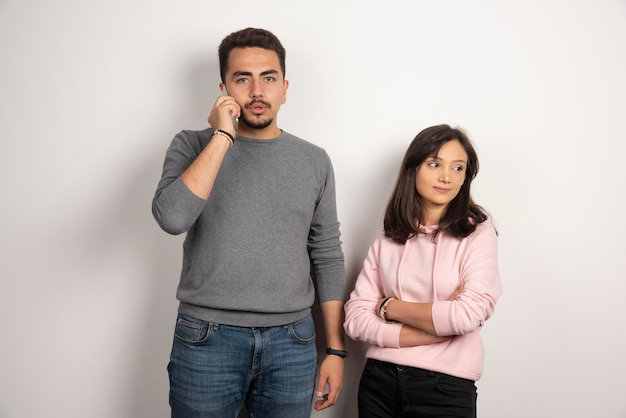 Femme debout tandis que l'homme parle avec téléphone.