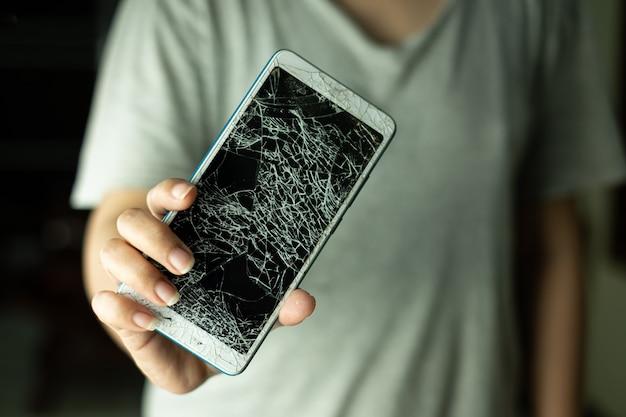 La femme debout et tenant l'écran du smartphone est fissurée