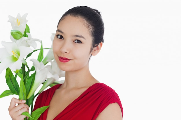 Femme debout en tenant des fleurs