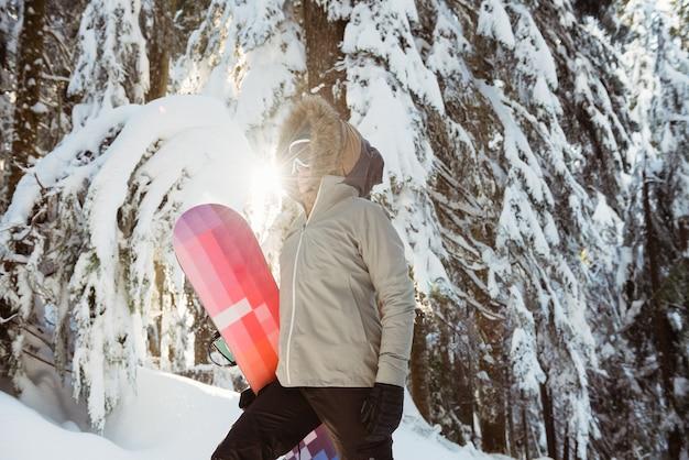 Femme debout et tenant un snowboard