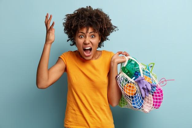 Femme avec des déchets plastiques dans un sac en filet