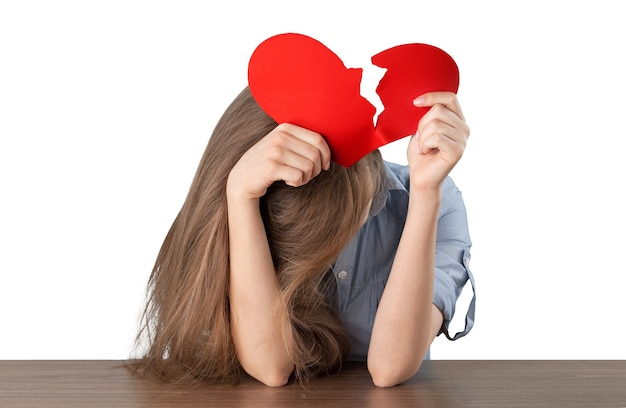 Femme déchirant un coeur de papier isolé