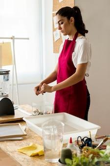 Femme, déchirer, papier, sur, verre, récipient, près, plateau