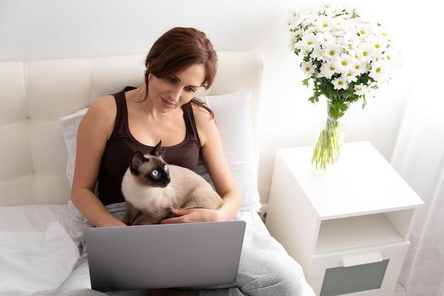 Femme décontractée à l'aide d'un ordinateur portable avec son chat siamois dans la chambre avec des fleurs. la vie avec un animal de compagnie.