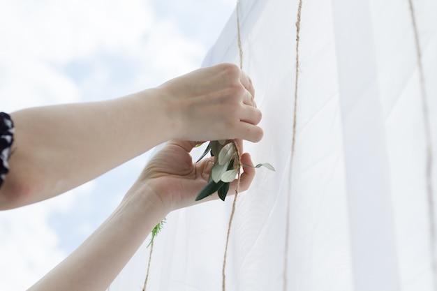 Femme décorant une belle arche de mariage blanc