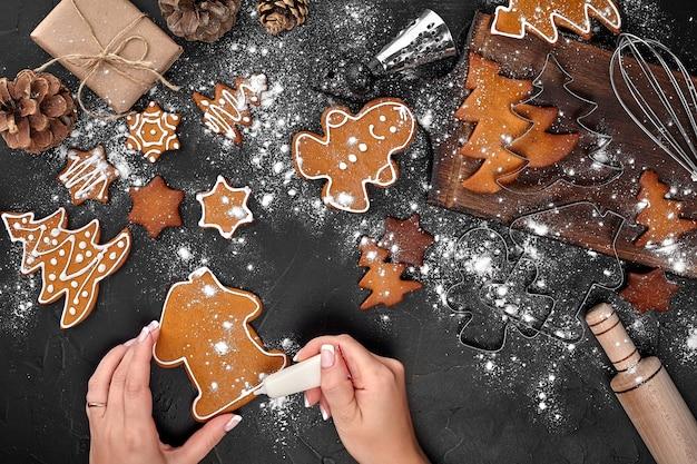 Femme décorant des biscuits de noël en pain d'épice avec du sucre glace sur fond sombre. concept de vacances, de célébration et de cuisine. concept de préparations de noël. vue de dessus avec espace de copie.