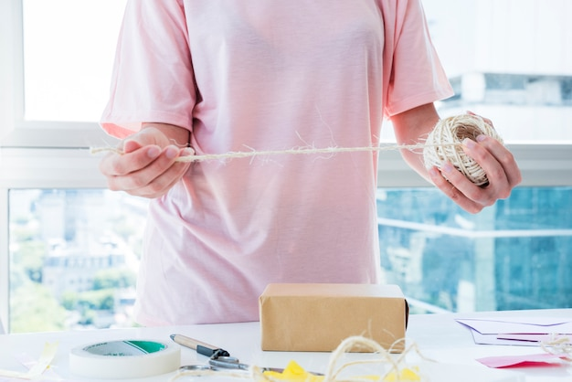 Femme décorant la boîte avec du fil sur table