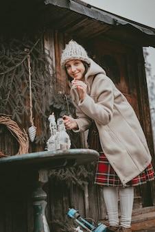 La femme de décoration de vacances crée une atmosphère de noël en plein air rustique minimaliste moderne à partir de matériaux écologiques naturels de style scandinave. des idées pour décorer le nouvel an de vos propres mains à la main.