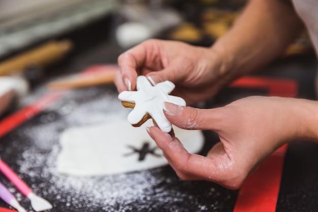 Femme décore des biscuits de pain d'épice de noël avec un flocon de neige glaçage sucre. cadeau de noël, pain d'épices maison