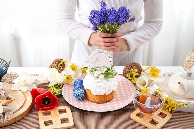 Une femme décore une table avec des friandises de labour avec des fleurs. concept de vacances de pâques.