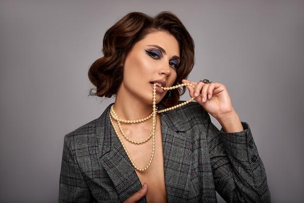 Femme décorée de perles. bijoux sur le cou et les mains, les doigts. sur un mur gris dans une veste. concept pour les bijouteries.