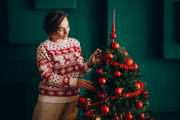 Femme décorer un arbre de noël avec des jouets rouges