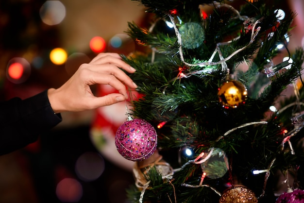 Femme décorer un arbre de noël