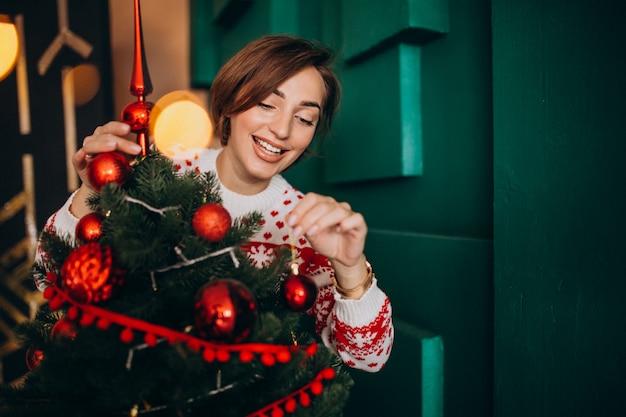 Femme décorer un sapin de noël avec des boules rouges