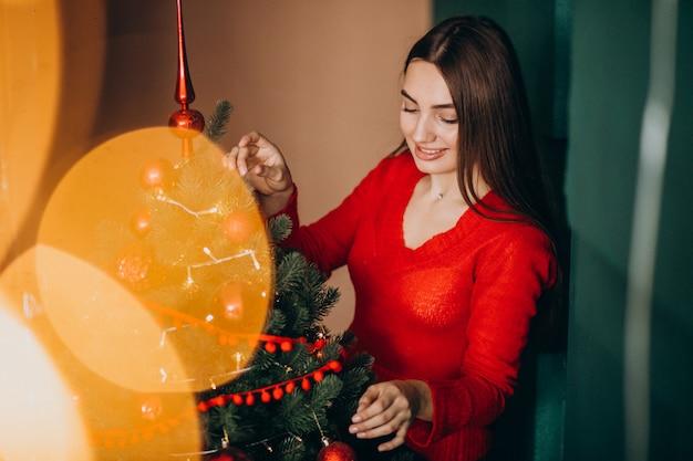 Femme décorer un sapin de noël à noël