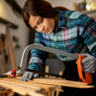 Femme, découper des planches de bois
