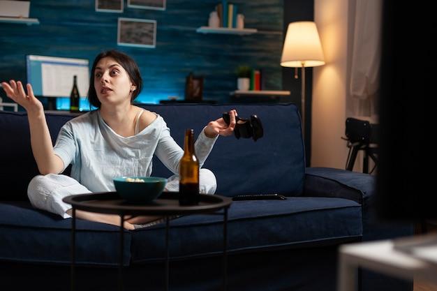 Femme déçue en colère tenant une manette de jeu jouant à des jeux vidéo de football