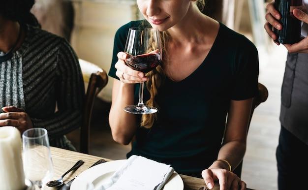 Femme dégustant du vin rouge dans un restaurant chic