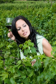Femme dégustant du vin de ses caves dans un vignoble