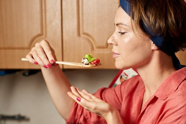 Femme, dégustation, salade, dans cuisine