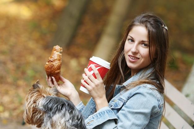 Femme déjeune en se promenant avec son chien