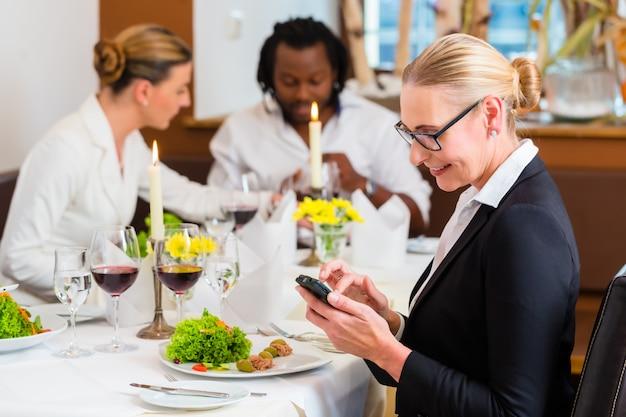 Femme, déjeuner affaires, vérification, courrier, téléphone