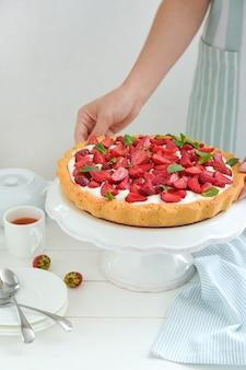 Femme avec un délicieux gâteau aux fraises sur le stand