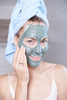 Femme, demande, masque, hydrater, peau, crème, figure, regarder, salle bains, miroir fille en prenant soin de son hydratant de superposition de teint. soin spa de soin.