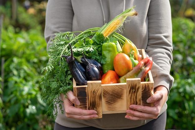 Femme démontrant une caisse en bois avec divers légumes une boîte en bois remplie de légumes frais