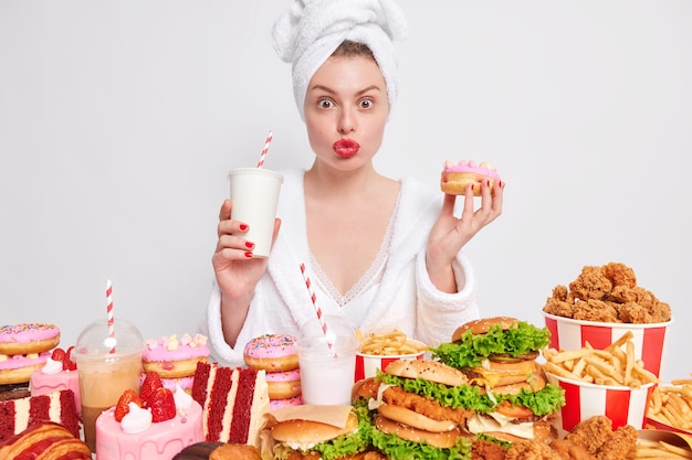 La femme a la dent sucrée boit du soda et mange des beignets garde les lèvres rouges pliées dans le baiser a une frénésie alimentaire s'efforce de délicieux aliments riches en calories pendant le week-end