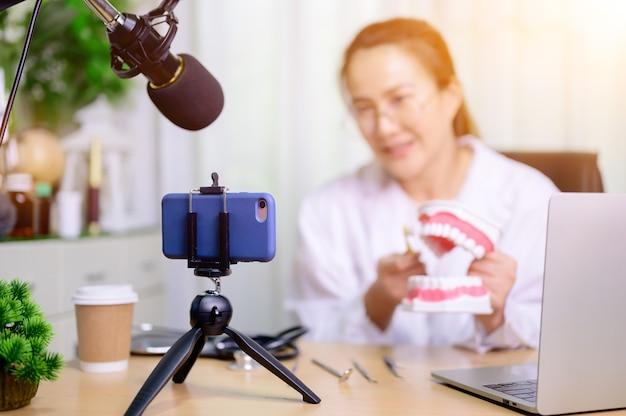 Femme dentiste asiatique travaillant en ligne à la maison. enregistrement d'une vidéo de blog pour un tutoriel sur le brossage des dents. dentisterie et soins dentaires.