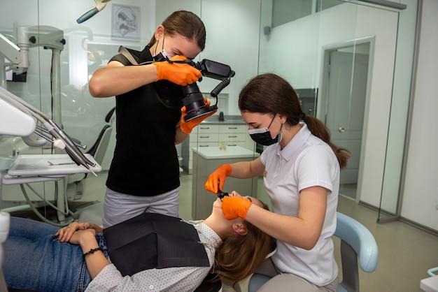 Femme dentiste et assistante avec appareil photo spécial avec anneau de flash sans ombre faisant des photos de patients sourire après le traitement.