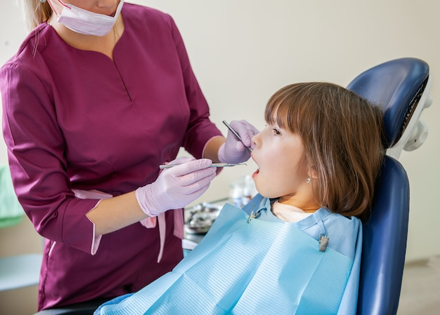 Femme dentiste en cabinet dentaire traite les dents avec un patient