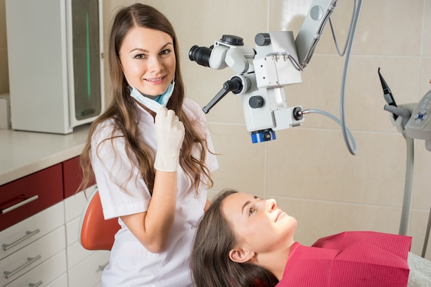 Femme dentiste dans son bureau traitant une patiente
